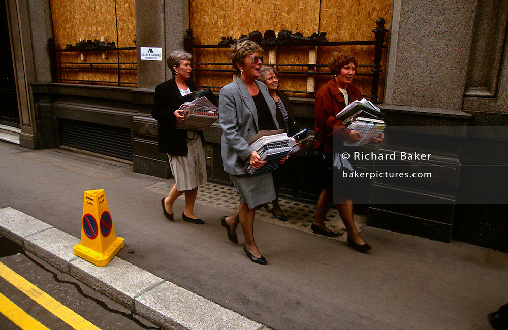 City workers carry office possessions including trays and files that were damaged by the IRA bomb that devastated the City of London's Bishopsgate area in 1993. Allowed to return to their desks to recover their data and working paperwork, they walk through the ancient streets en route to new emergency office elsewhere in the capital. The Irish Republican Army (IRA) exploded a truck bomb on Bishopsgate. Buildings up to 500 metres away were damaged with one and a half million square feet (140,000 m) of office space being affected and over 500 tonnes of glass broken. Repair costs reached approx £350 million. It was said that Roman remains could be viewed at the bottom of the pit the bomb created. One person was killed when the one ton fertiliser bomb detonated directly outside the medieval St Ethelburga's church.