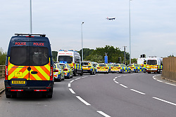 © Licensed to London News Pictures. 13/09/2021. Staines, UK. A plane passes over police vehicles parked up on Poyle Interchange as protester's from climate campaign 'Insulate Britain', an offshoot of Extinction Rebellion (XR), block the clockwise slip road at Poyle Interchange/junction 14, M25 London Orbital Motorway. Photo credit: Peter Manning/LNP
