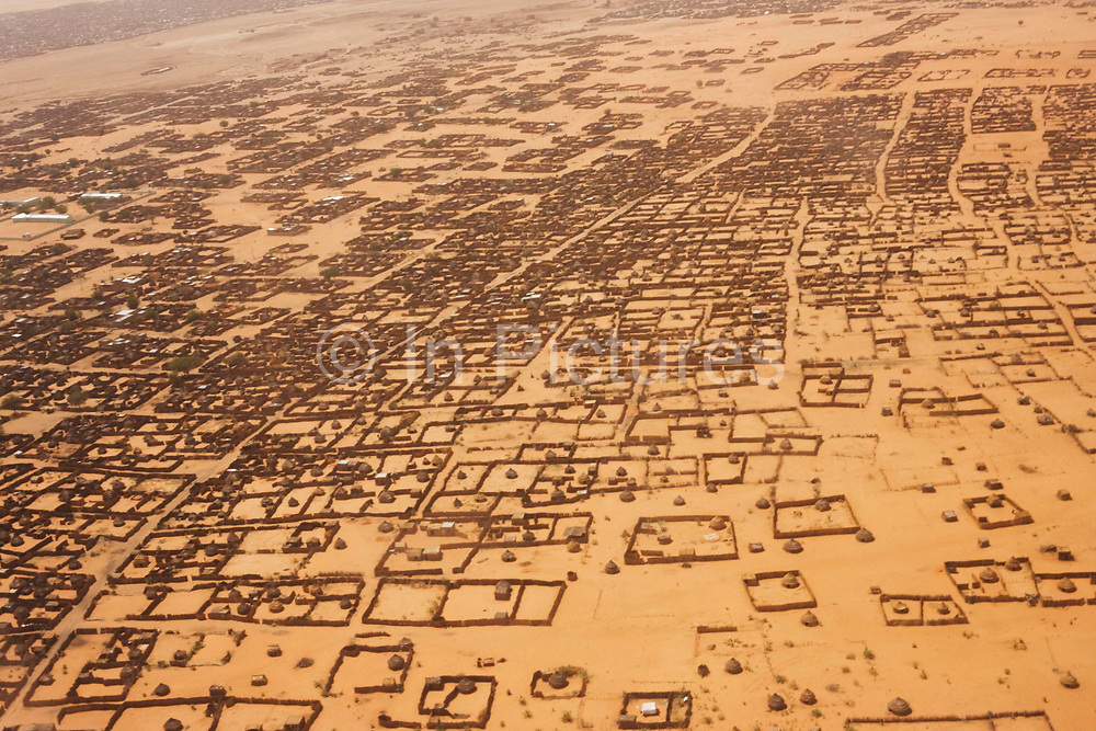Aerial view of Al Fasher (also spelled, Al-Fashir) the front-line town in north Darfur during a tribal war resulting from colonial land-use. Basic housing is seen against the barren and scorched red earth in this area of south-western Sudan. The Sahara is the world's largest hot desert. At over 9,000,000 square kilometers (3,500,000 sq mi), it covers most of Northern Africa, making it almost as large as the United States or the continent of Europe.