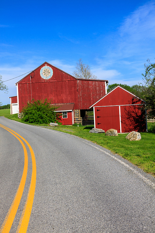 Hamburg, PA, USA- May 12, 2012: A red barn on a rural road with a large round Hex sign in Berks County, PA.