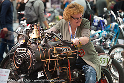 Sara Viney of AMD with Rene van Tuil of Revatu Customs in Eck en Wiel, Netherlands and his air powered Honda 98cc 4-stroke with compressor pump 2-wheeled oddity that was on display in the AMD World Championship of Custom Bike Building in the custom themed Hall 10 at the AMD World Championship of Custom Bike Building show in the custom dedicated Hall 10 at the Intermot Motorcycle Trade Fair. Cologne, Germany. Saturday October 8, 2016. Photography ©2016 Michael Lichter.