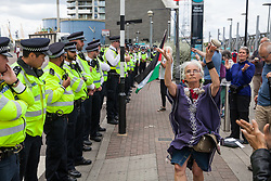 London, UK. 3 September, 2019. Metropolitan Police officers form a cordon around human rights activists protesting outside ExCel London on the second day of a week-long carnival of resistance against DSEI, the world's largest arms fair. The second day's events were organised around a theme of No Faith In War and were attended by representatives of many faith groups including a significant number of Quakers.