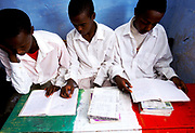 Three boys study in a secondary school on a desk painted in Somaliland's national colours. Hargeisa, capital of the self declared independent country of Somaliland