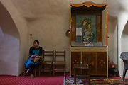 A local woman sits next to a shrine with the Virgin Mary and Jesus at St Tawdros (St Theodore's) Coptic Orthodox Christian Monastery, Luxor, Nile Valley, Egypt. The Copts are an ethno-religious group in North Africa and the Middle East, mainly in the area of modern Egypt, where they are the largest Christian denomination. Christianity was the religion of the vast majority of Egyptians from 400–800 A.D. and the majority after the Muslim conquest until the mid-10th century. Today, there are an extimated 9-15m Copts in Egypt.