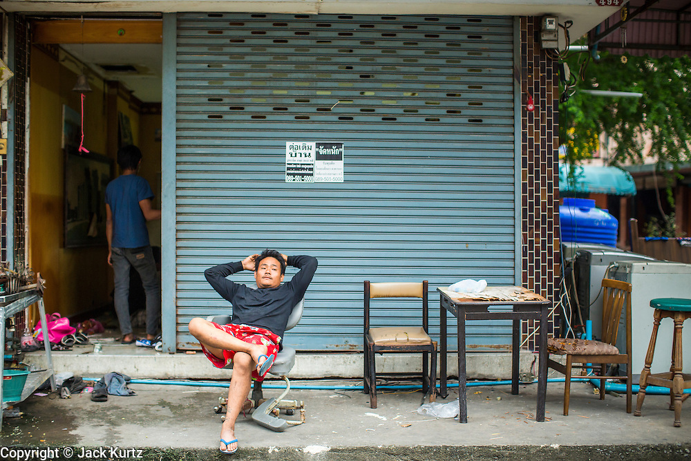 """12 DECEMBER 2012 - BANGKOK, THAILAND:  A demolition worker relaxes in front of the empty business he lives in while he works at """"Washington Square"""" a notorious entertainment district off Sukhumvit Soi 22 in Bangkok. Demolition workers on many projects in Thailand live on their job site tearing down the building and recycling what can recycled as they do so until the site is no longer inhabitable. They sleep on the floors in the buildings or sometimes in tents, cooking on gas or charcoal stoves working from morning till dark. Sometimes families live and work together, other times just men. Washington Square was one of Bangkok's oldest red light districts. It was closed early 2012 and is being torn down to make way for redevelopment.    PHOTO BY JACK KURTZ"""