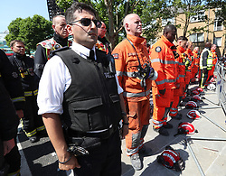 Members of the emergency services observe a minute's silence near to Grenfell Tower in west London after a fire engulfed the 24-storey building on Wednesday morning.