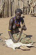 Daasanach Tribe Village woman curing animal skin to leather