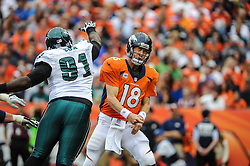 Sep 29, 2013; Denver, CO, USA; Denver Broncos quarterback Peyton Manning (18) reacts as he is about to be hit by Philadelphia Eagles defensive end Fletcher Cox (91) during the game at Sports Authority Field at Mile High. Mandatory Credit: John Geliebter-Philadelphia Eagles