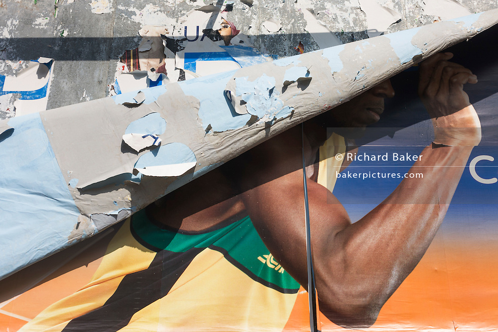 Layers of an advertising billboard have peeled back to reveal the arm of Olympic athlete Usain Bolt in south London