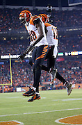 Cincinnati Bengals wide receiver A.J. Green (18) leaps and celebrates a hip bump with Cincinnati Bengals wide receiver Mohamed Sanu (12) after Green catches a five yard first quarter touchdown pass good for a 7-0 Bengals lead during the 2015 NFL week 16 regular season football game against the Denver Broncos on Monday, Dec. 28, 2015 in Denver. The Broncos won the game in overtime 20-17. (©Paul Anthony Spinelli)