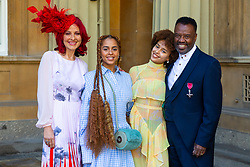 Musician David Grant proudly displays his OBE for services to music, accompanied by his wife Carrie, left and actress daughters Olive Gray, 24 (Save Me, Sex Education) and Talia, 17 (Hollyoakes) following an investiture ceremony at Buckingham Palace in London. London, March 14 2019.