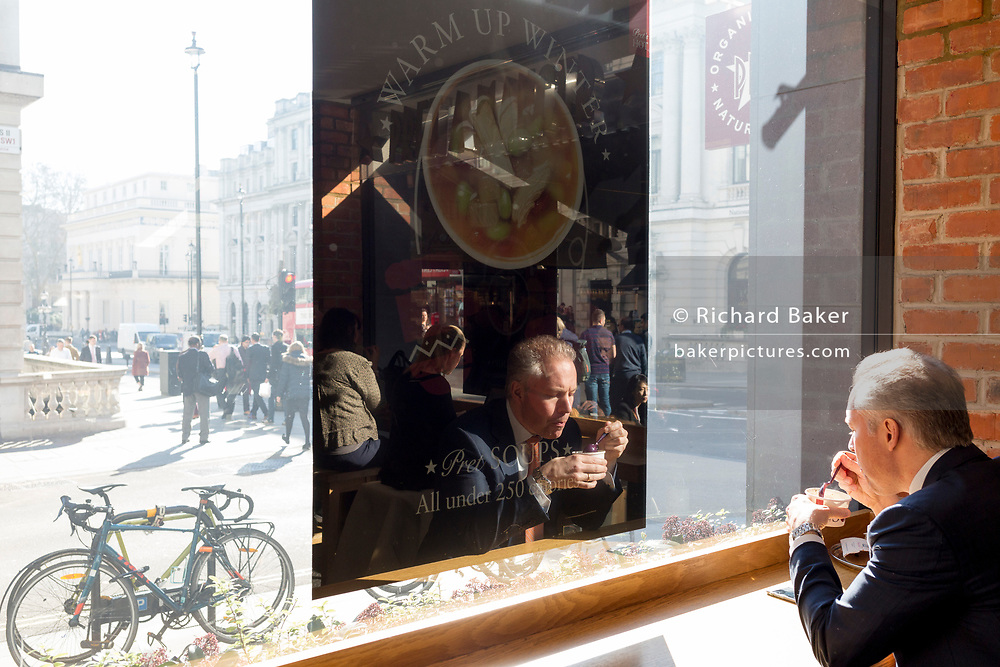 A man eats his lunch in the sunlit window of a Pret a Manger, on 25th February 2019, in London, England.