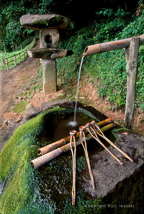 Water basin at entrance to Kamosu-jinja (shrine), Matsue city, Shimane Prefecture, Japan. Shrine visitors use the long-handled hishaku (diipper) in a purifying ritual before entering the shrine grounds.
