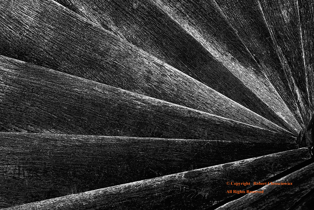 Spiral (B&W): The unusual birds-eye view of worn wooden stairs of a spiral staircase, Singapore.
