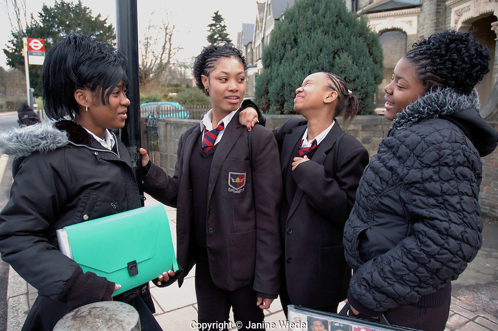 A group of sixth form girls looking at homework while waiting at bus stop on their way home from school..