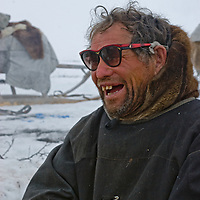 North of the Arctic Circle in Russia, nomadic Komi reindeer herder Stass Pan'kov jokes with his companions as he waits for the reindeer herd to arrive to pull his sleds.