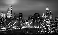 A monochrome look at the New York City skyline and the Queensboro bridge at night on a Fall evening as the city lights light up the stormy clouds overhead.