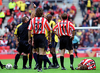 Arsenals Patrick Vieira is shown the red card by referee Steve Dunn as injured Sungerland player Darren Williams lies on the ground. Sunderland 1:0 Arsenal, 19/8/2000. Credit Colorsport / Stuart MacFarlane