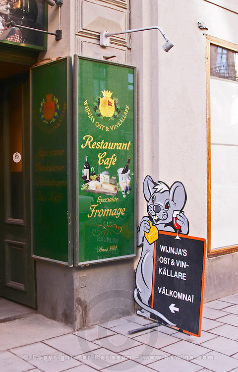 An oldfashioned painted glass sign outside the cheese shop Wijnjas Cheese and Wine Cellar with painted decorations and a funny sign with a mouse with cheese and a glass of wine. Stockholm, Sweden, Sverige, Europe