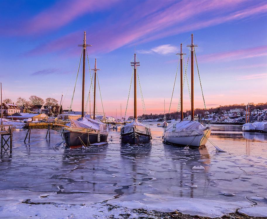 Windjammers moored in icy harbor in winter, dusk, Camden, ME