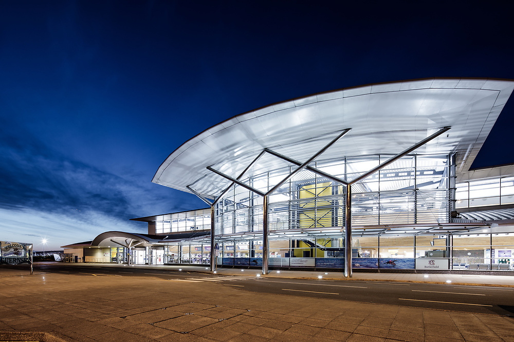 The exterior of the Guernsey airport arrivals and departures halls at dusk in the Channel Islands
