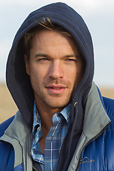portrait of a handsome man outdoors wearing a hood