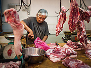 17 NOVEMBER 2016 - GEORGE TOWN, PENANG, MALAYSIA: A butcher cuts pork in a market in George Town, Penang, Malaysia. George Town is a UNESCO World Heritage city and wrestles with maintaining its traditional lifestyle and mass tourism. Malaysia is predominantly Muslim and pork sellers in Penang have their own section of the market so halal consumers don't have to touch pork products.       PHOTO BY JACK KURTZ