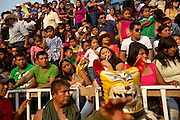 The crowd watches as men fight with jaguar masks and rope in the plaza during the fiestas in Zitlala, Mexico.  In this village they  maintain the ancient tradition of fighting in jaguar masks. This is a pre-Columbian tradition in which the blood and sweat that fall to the ground are an offering to earth.  In return for their blood the people ask the gods for rain.  In Zitlala they fight each other with rope.