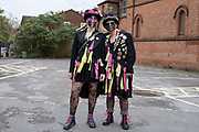 Morris dancers from Beorma Border Morris dancing troupe in Kings Heath pose for a photograph after visiting a local friend on May Day under Coronavirus lockdown on 1st May 2020 in Birmingham, England, United Kingdom. These two women from the Beorma Morris are wearing their full costumes including rags and tatters, fishnet tights and feathers, and with distinctive blackened faces. Many morris sides through history blackened their faces, and Blacking up is reputed to have been as some form of disguise because the performers many of whom had jobs in agriculture, were begging, which was both illegal and could bring them shame. If so, the black face must have been a custom that saved face on the part of dancers and audience alike. The Coronavirus or Covid-19 is a new respiratory illness that has not previously been seen in humans. While much or Europe has been placed into lockdown, the UK government has put in place more stringent rules as part of their long term strategy, and in particular social distancing.