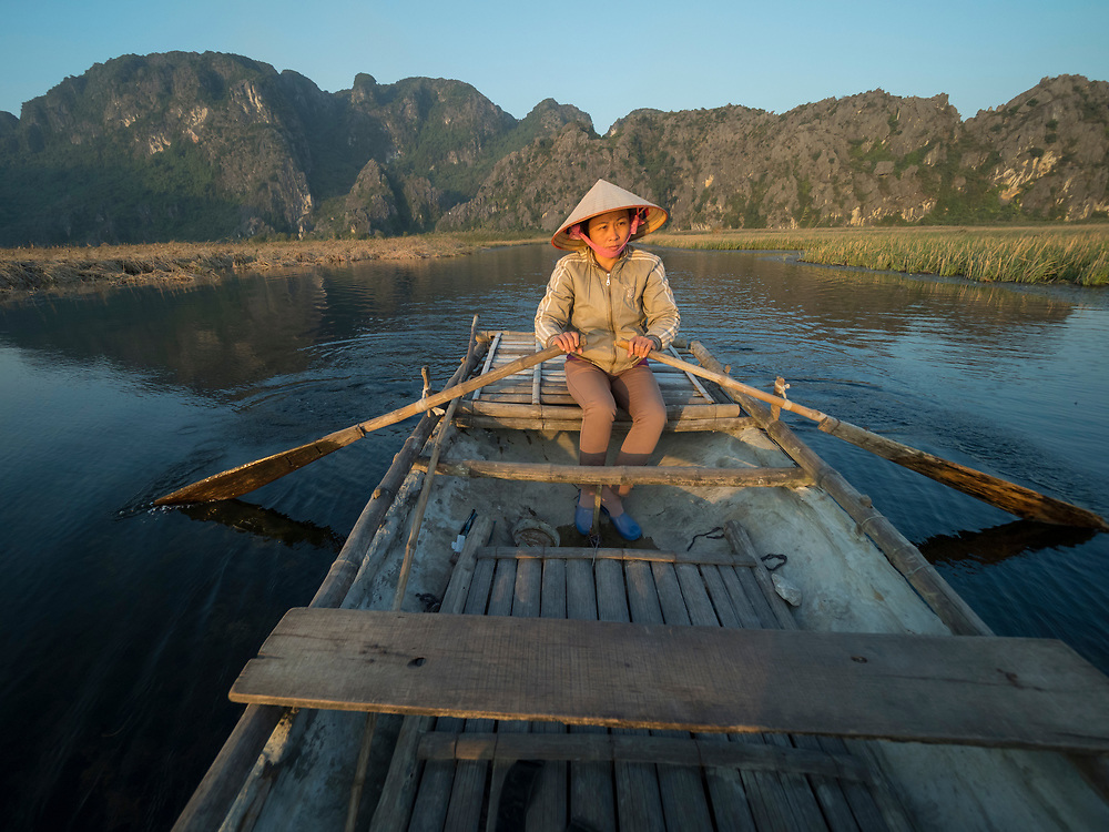 Asia, Vietnam, Van Long Nature Reserve. Asia, Vietnam, Hanoi, old quarter, Woman wearing conical Non La hat, rowing a boat. Editorial Use Only.