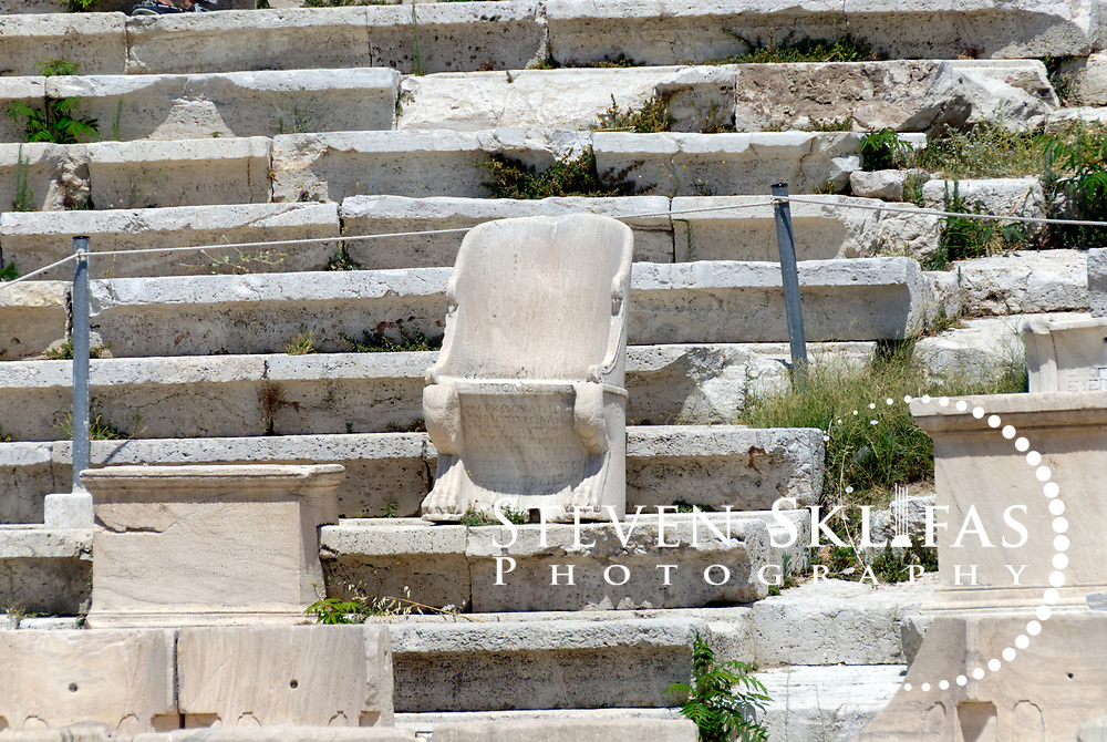 Athens. Greece. View of the central throne of the priest of Dionysos Eleutherios at the Theatre of Dionysos on the southern slope of the Acropolis in Athens. Throne is armed chair with lion's claw feet and has inscribed the owner's name. The Theatre was originally established in the 6th century BC and enlarged and improved over the Classical, Hellenistic and Roman periods and was the first theatre built of stone. The famous tragedies of Aeschylus, Sophocles and Euripides and the comedies of Aristophanes were first performed here in the 5th century BC. What is seen today is largely from the 4th century BC during the time of Lycurgus, who controlled public investment in Athens from 338 to 324 BC. The structure has 25 surviving tiers of seats from the original 65 and had a capacity to seat 17,000 spectators. The Stage front is Roman and is represented by the Bema of Phaedrus, which has 2nd century AD decorative reliefs showing scenes in the life of Dionysus, god of wine and patron god of the Greek stage.
