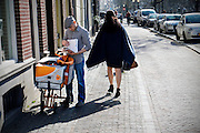 In Utrecht passeert een vrouw met een rok een postbesteller van PostNL die de post aan het uitzoeken is.<br /> <br /> In Utrecht a woman with a skirt passes a postman of PostNL who is browsing in the mail.