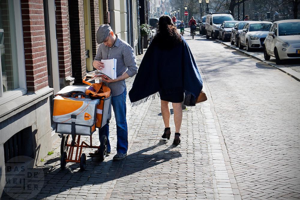 In Utrecht passeert een vrouw met een rok een postbesteller van PostNL die de post aan het uitzoeken is.<br /> <br /> In Utrecht a woman with a skirt passes a postman of PostNL who is browsing in the mail.