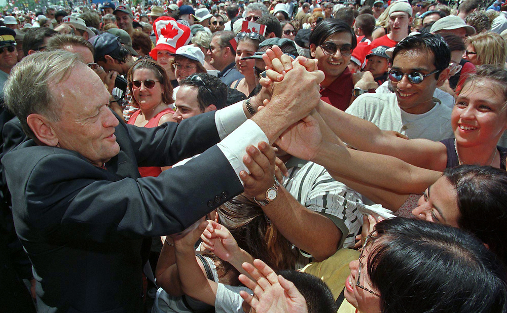 Canadian Prime Minister Jean Chretien (L) reaches out to shake hands with the crowd during Canada Day celebrations on Parliament Hill in Ottawa, July 1. Thousands of people came out to celebrate Canada's 132nd birthday.  REUTERS/Jim Young