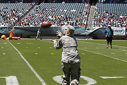 An Army servicewoman catches a football on the field before the Philadelphia Eagles NFL football training camp practice in Philadelphia, Monday, August 5, 2013. (Photo by Brian Garfinkel)