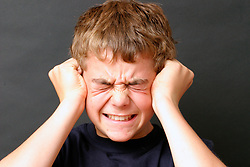 Portrait of boy aged 12 looking angry or annoyed UK