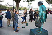 Children interact with a living statue artist. On this part of the Southbank in London, UK there are a number of these street performers. This one in particular is incredible, never once blinking. The South Bank is a significant arts and entertainment district, and home to an endless list of activities for Londoners, visitors and tourists alike.