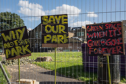 London, UK. 14th August, 2021. Signs are displayed on a fence objecting to Southwark Council's plans to develop Peckham Green as public housing. Peckham Green is a 1.4-acre public park off Peckham High Street, one of the most polluted roads in London, in a borough which is ranked fifth-worst in London and eighth-worst in the UK for easy access to green space, and local residents and campaigners have been protesting that they were not consulted by Southwark Council in relation to its plans.