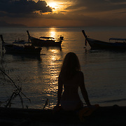 Silhouette of a girl sitting on a fallen tree on Sunrise beach against rising sun, Ko Lipe, Thailand