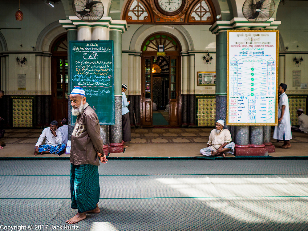 """24 NOVEMBER 2017 - YANGON, MYANMAR: A Muslim man in Surtee Sunni Jumma Mosque in Yangon. Many Muslims in overwhelmingly Buddhist Myanmar feel their religion is threatened by a series of laws that target non-Buddhists. Under the so called """"Race and Religion Protection Laws,"""" people aren't allowed to convert from Buddhism to another religion without permission from authorities, Buddhist women aren't allowed to marry non-Buddhist men without permission from the community and polygamy is outlawed. Pope Francis is to arrive in Myanmar next week and is expected to address the persecution of the Rohingya, a Muslim ethnic minority in western Myanmar. Some Muslims and Christians are concerned that if the Pope's comments take too strong of pro-Rohingya stance, he could exacerbate religious tensions in the country.  PHOTO BY JACK KURTZ"""