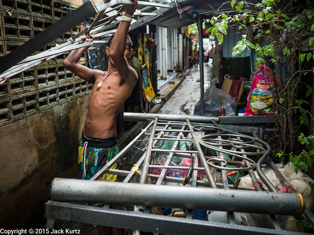 28 SEPTEMBER 2015 - BANGKOK, THAILAND:  A man moves his bed out of him home near Wat Kalayanamit. Fifty-four homes around Wat Kalayanamit, a historic Buddhist temple on the Chao Phraya River in the Thonburi section of Bangkok, are being razed and the residents evicted to make way for new development at the temple. The abbot of the temple said he was evicting the residents, who have lived on the temple grounds for generations, because their homes are unsafe and because he wants to improve the temple grounds. The evictions are a part of a Bangkok trend, especially along the Chao Phraya River and BTS light rail lines. Low income people are being evicted from their long time homes to make way for urban renewal.   PHOTO BY JACK KURTZ