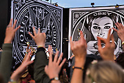 Making a crowd salute while dancing in front of Shepard Fairey Obey posters in the Hell area, Shangri La field, Glastonbury Festival 2016. The Glastonbury Festival is the largest greenfield festival in the world, and is now attended by around 175,000 people. Its a five-day music festival that takes place near Pilton, Somerset, United Kingdom. In addition to contemporary music, the festival hosts dance, comedy, theatre, circus, cabaret, and other arts. Held at Worthy Farm in Pilton, leading pop and rock artists have headlined, alongside thousands of others appearing on smaller stages and performance areas.