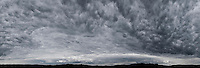 Dark clouds over hilly silhouette