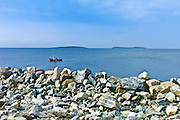 Fishing boat with Saltee Islands in background and sea defences, Kilmore, County Wexford, Ireland