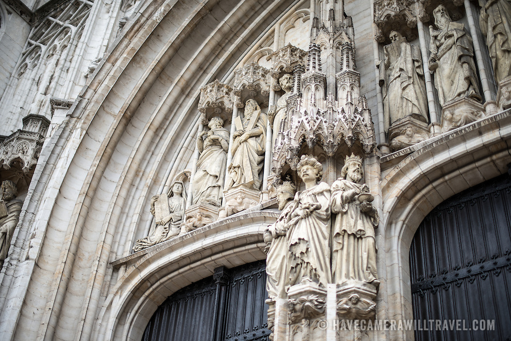 Statues over the main doorway at the Cathedral of St. Michael and St. Gudula (in French, Co-Cathédrale collégiale des Ss-Michel et Gudule). A church was founded on this site in the 11th century but the current building dates to the 13th to 15th centuries. The Roman Catholic cathedral is the venue for many state functions such as coronations, royal weddings, and state funerals. It has two patron saints, St Michael and St Gudula, both of whom are also the patron saints of Brussels.