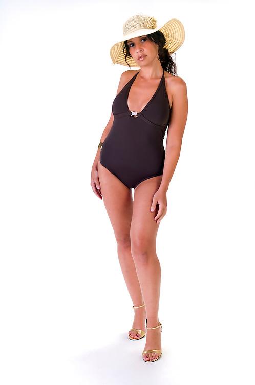 Portrait of hispanic woman wearing beach hat, standing in studio.