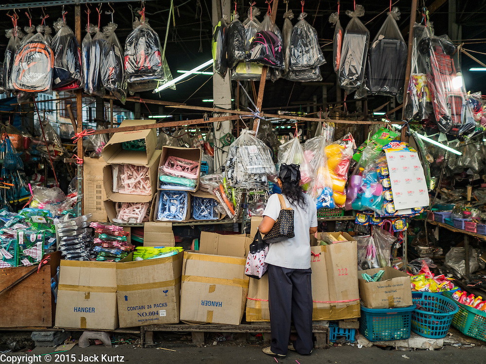 14 DECEMBER 2015 - BANGKOK, THAILAND: A woman shops in a dry goods shop in Bang Chak Market. The market closes permanently on Dec 31, 2015. The Bang Chak Market serves the community around Sois 91-97 on Sukhumvit Road in the Bangkok suburbs. About half of the market has been torn down. Bangkok city authorities put up notices in late November that the market would be closed by January 1, 2016 and redevelopment would start shortly after that. Market vendors said condominiums are being built on the land.       PHOTO BY JACK KURTZ