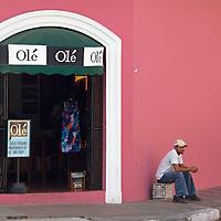 Central America, Nicaragua, Granada. Local man sits outside Ole Shop in Granada.