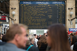 Detail of destinations on departures board and many passengers waiting for trains  at Gare du Nord railway station in Paris France