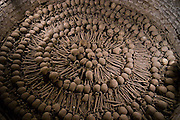 Neatly arranged human skulls and bones piled inside the catacombs below the Monasterio de San Francisco in Lima, Peru.